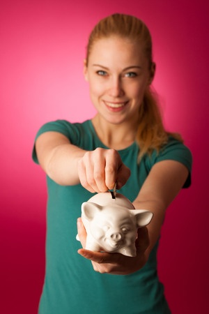 51503277 - woman with piggy bank in hands excited to safe save savings.